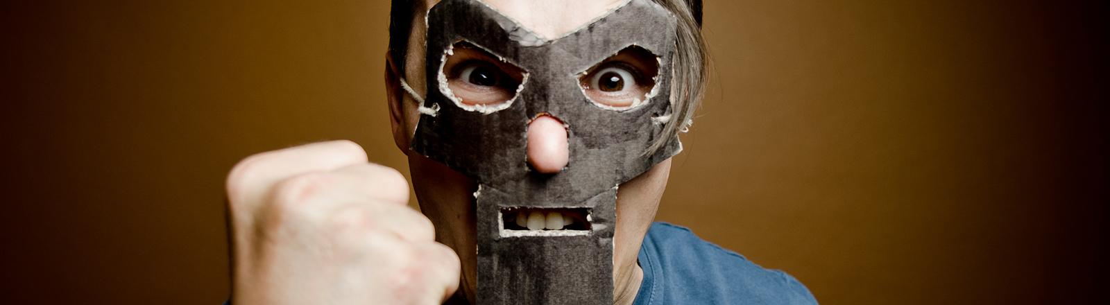 Mann mit Maske zeigt eine Faust