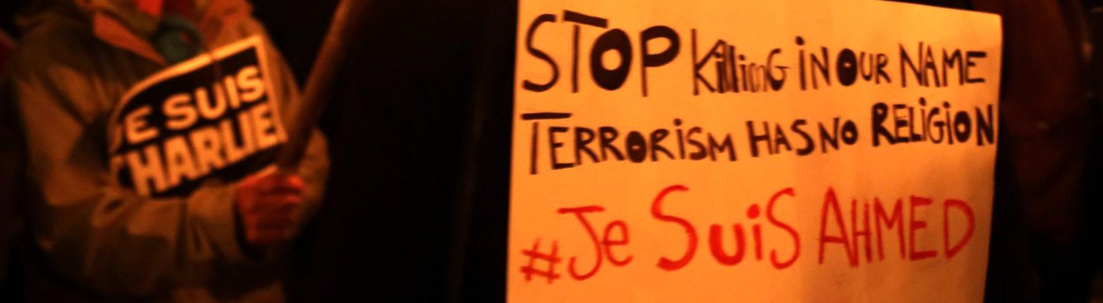 Auf einem Schild steht: Stoppt das Töten in unserem Namen. Terrorismus hat keine Religion. Je suis Ahmed