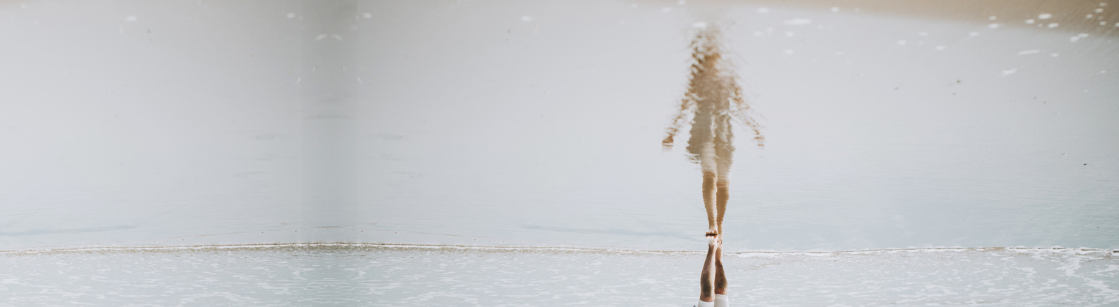 Eine Frau spiegelt sich im Wasser