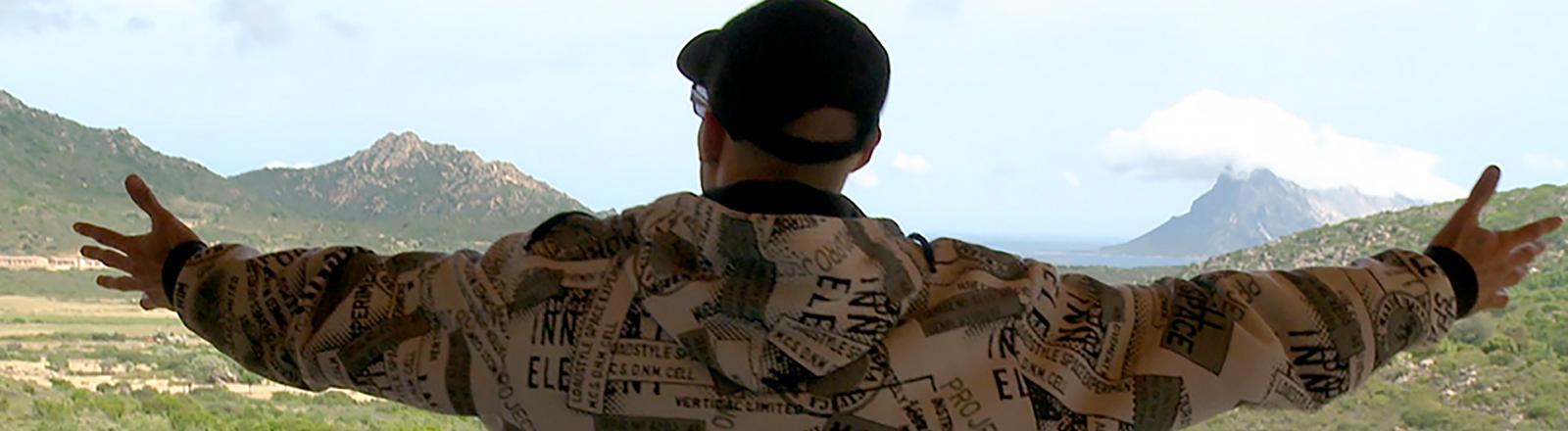 Filmszene: Mann breitet die Arme aus.