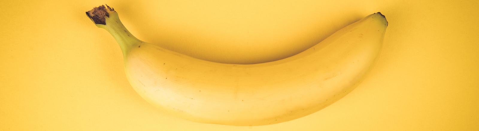 Gelbe Banane vor gelbem Hintergrund