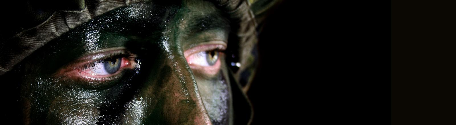 Ein Soldat mit Tarnhelm und Tarnfarbe im Gesicht