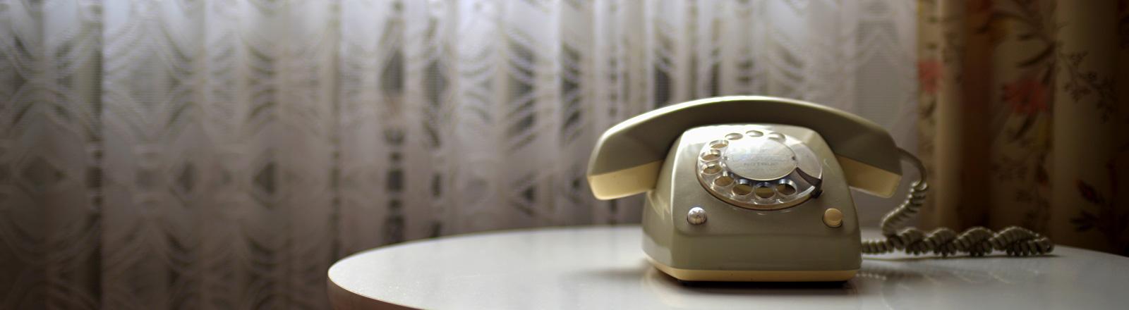 Ein Telefon aus den 70er Jahren auf einem Beistelltisch.