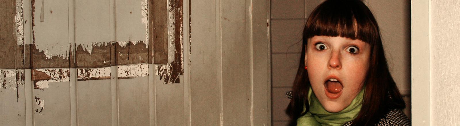 Eine junge Frau öffnet eine Tür und schaut erstaunt