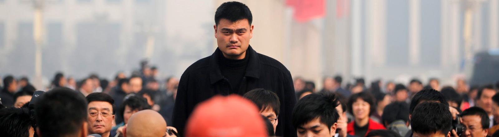 Yao Ming zwischen einer Horde Journalisten. Die meisten um ihn stehenden Menschen reichen nicht mal bis zu seiner Brust.