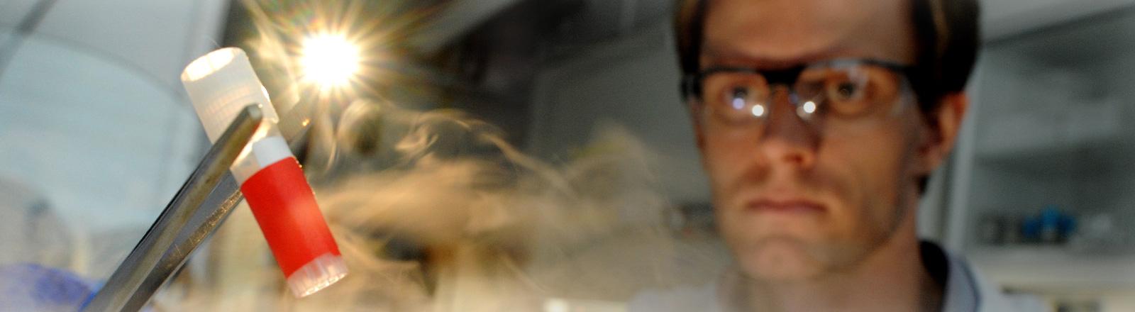 Ein Mann in einem Labor schaut gebannt auf ein Röhrchen, das aus einer dampfenden Schale emporgehalten wird