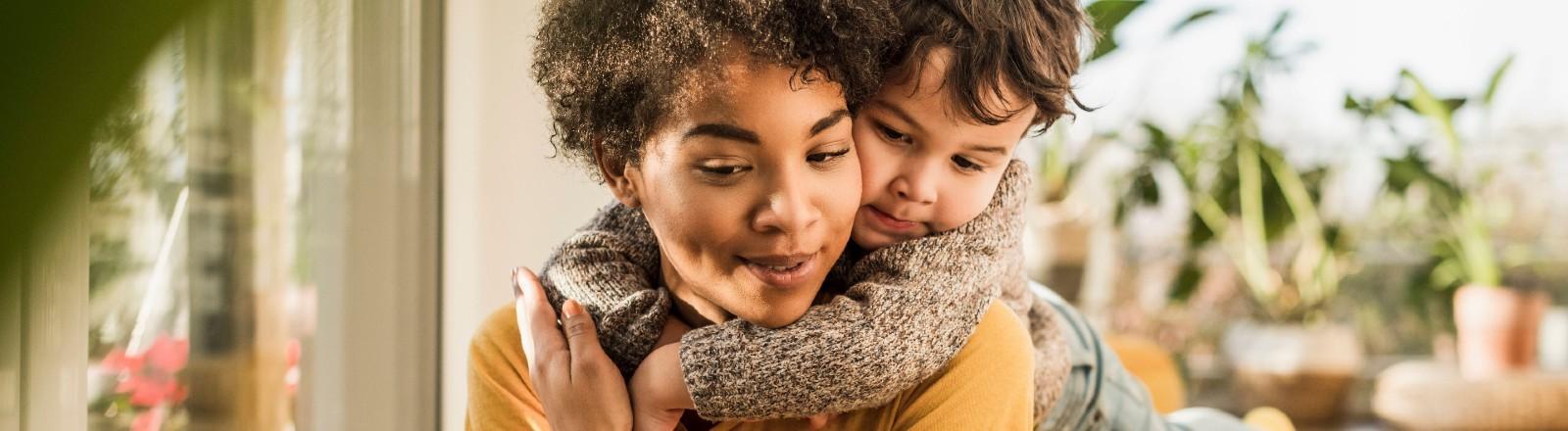 Eine junge Mutter kuschelt mit ihrem Kind.
