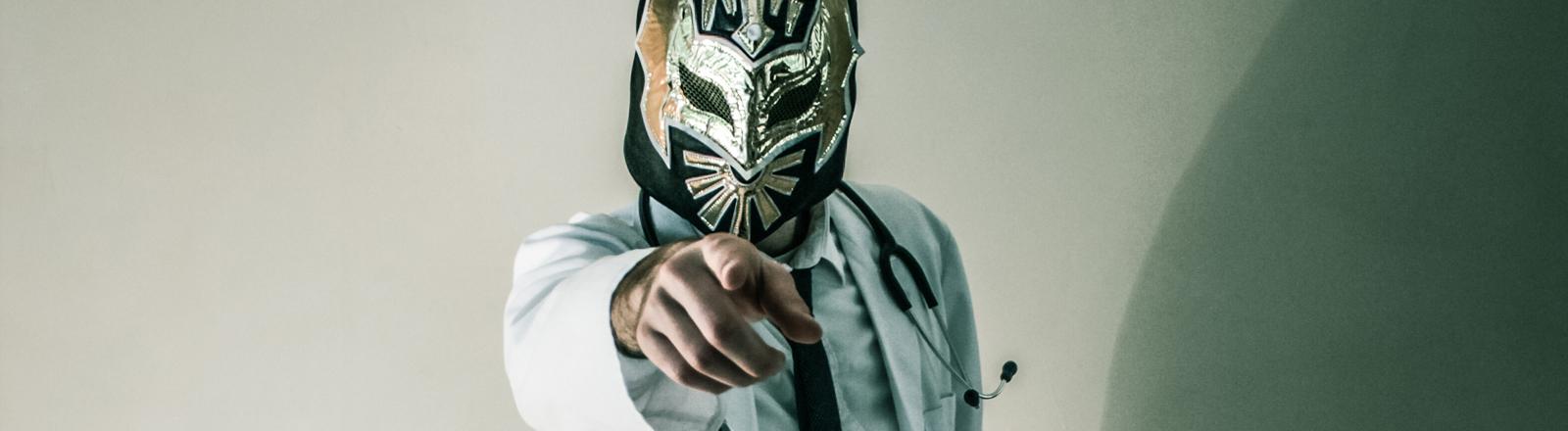 Arzt mit Wrestlermaske.