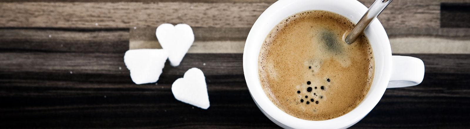 Eine Espressotasse mit Kaffe und drei Stück Würfelzucker in Form von Herzen.