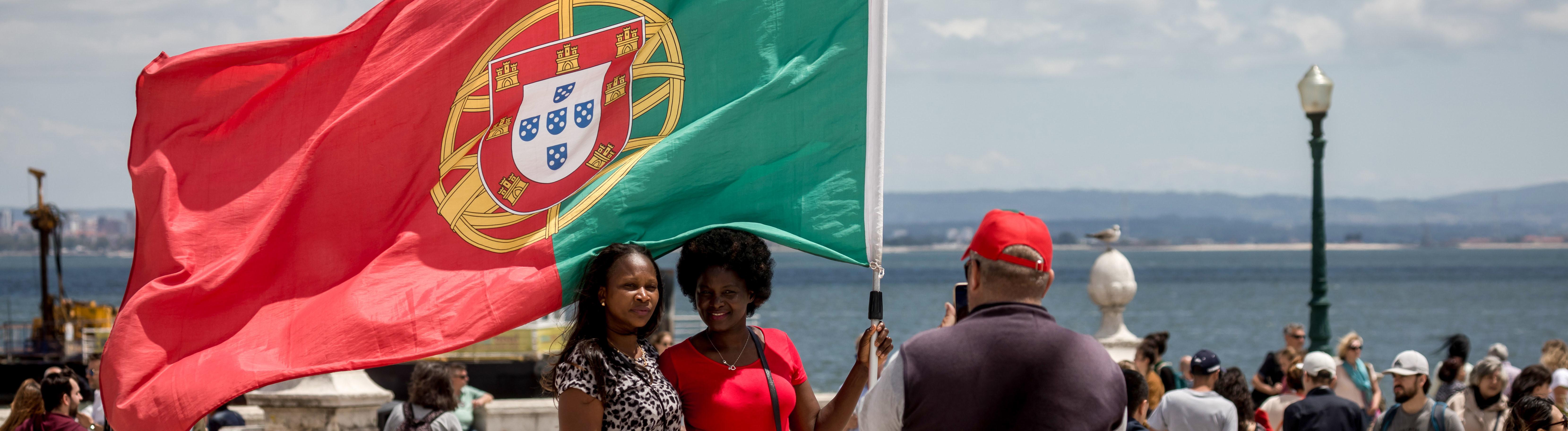 Frauen mit der Flagge Portugals auf einem Platz in Lissabon