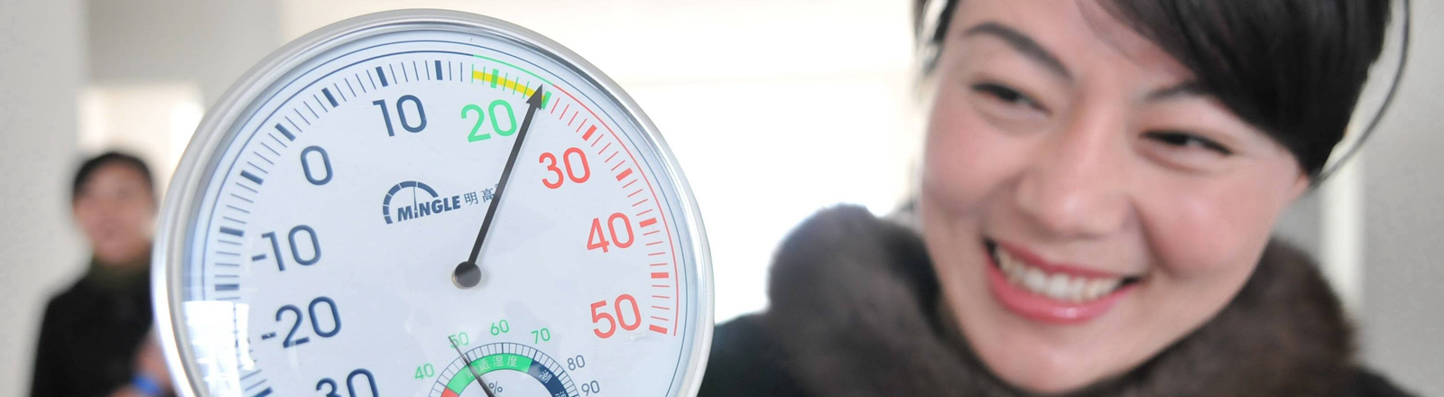 Frau mit Thermometer in der Hand