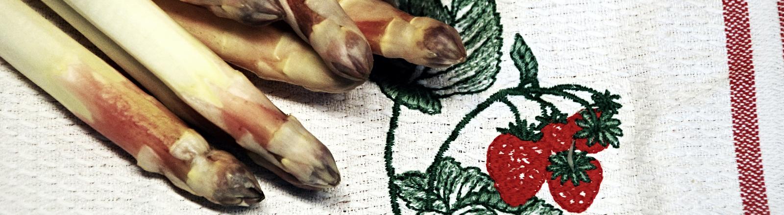 Frischer Spargel auf Küchentuch mit Erdbeermotiv