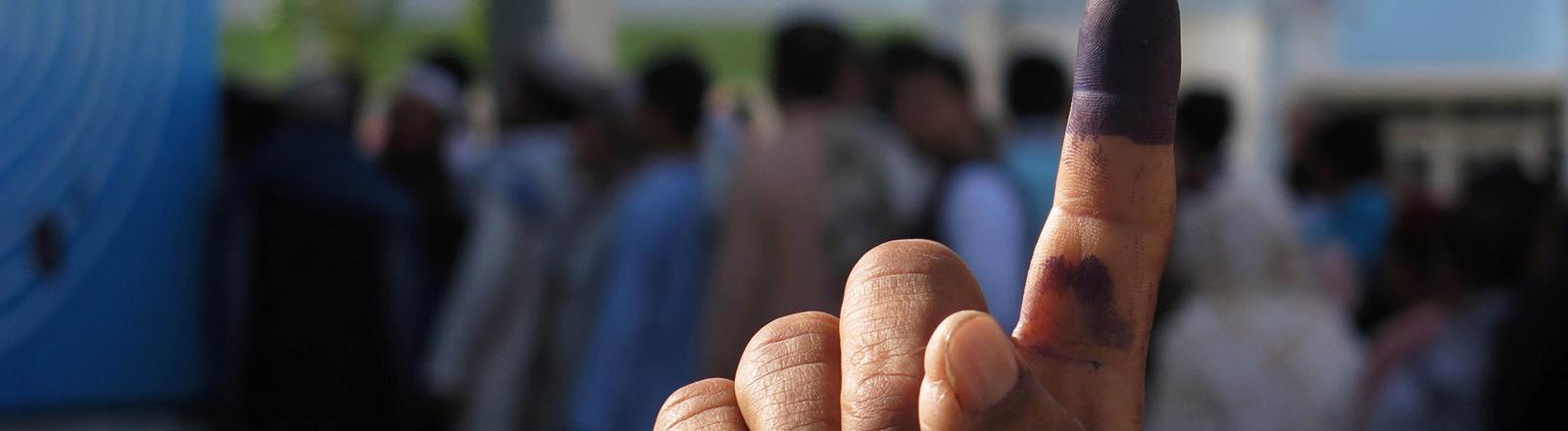 Eine Hand mit ausgestrecktem Zeigefinger wird in die Luft gehalten, der Finger ist blau eingefärbt. Im Hintergrund stehen Männer in einer Reihe. Bild: dpa