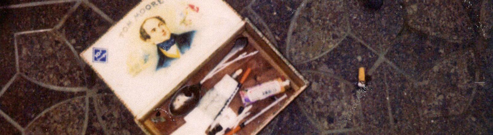Auf dem Boden liegt eine Box mit Drogenbesteck. Diese wurde im Haus von US-Sänger Kurt Cobain nach seinem Tod von der Polizei sichergestellt. Bild: dpa