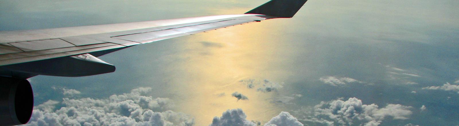 Eine Tragfläche eines Flugzeugs hoch über den Wolken.