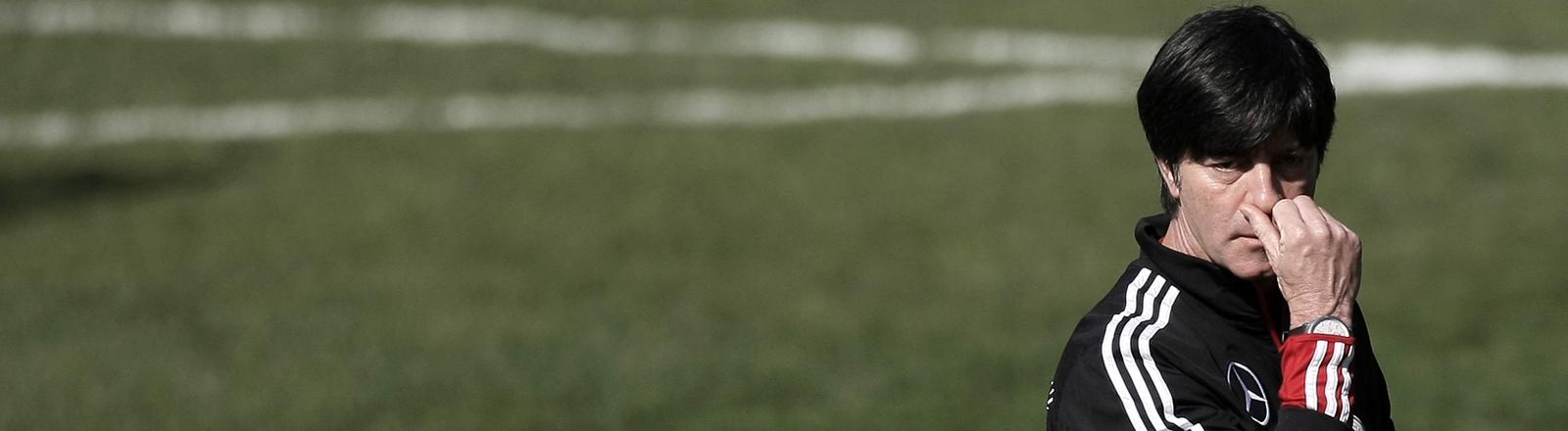 Bundestrainer Jogi Löw fasst sich an die Nase.