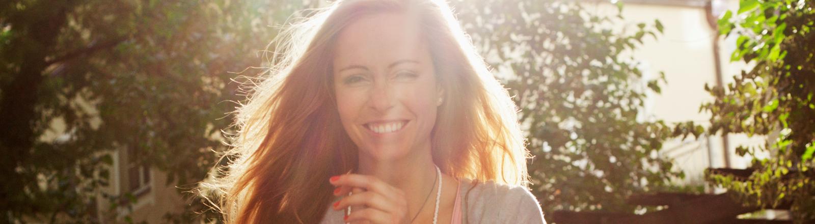 Christin Henkel steht im Gegenlicht und lacht, im Hintergrund sind ein Baum und ein Haus zu sehen. Sie hat lange, rötliche Haare.