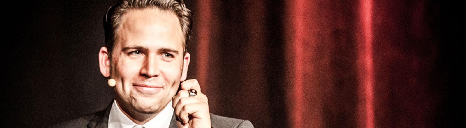 Comedian Christoph Tiemann vor einem roten Bühnenvorhang.