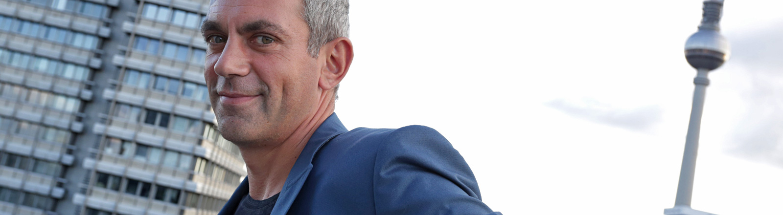 Wladimir Kaminer steht auf dem Dach des Hotels Indigo. Er blickt grinsend in die Kamera. Im Hintergrund sind ein Hochhaus und der Berliner Fernsehturm zu sehen; Bild: dpa