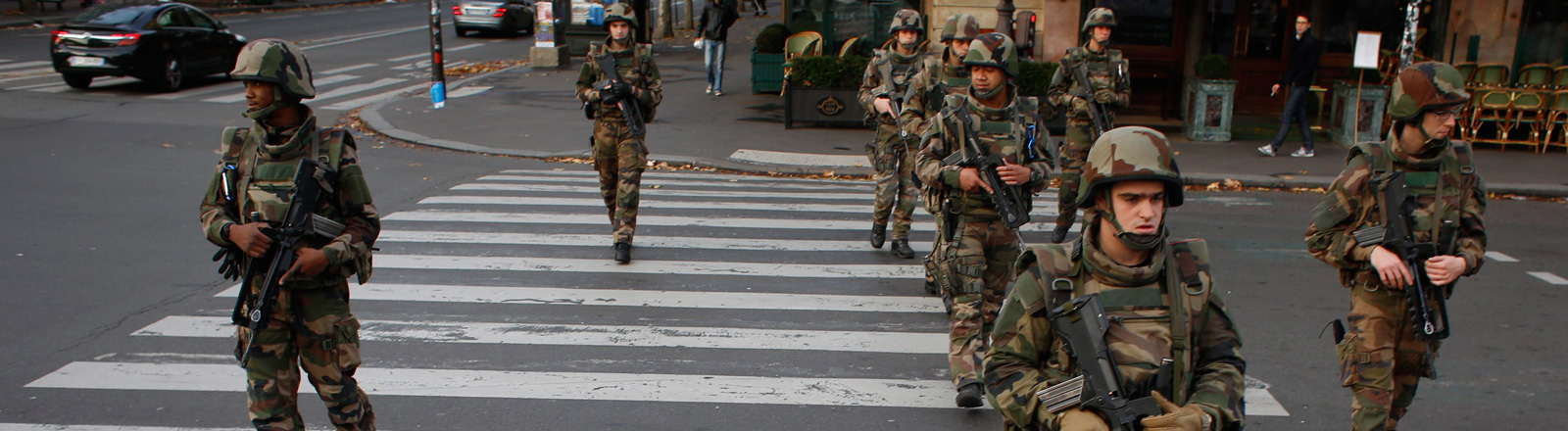Soldaten gehen in Paris über einen Zebrastreifen