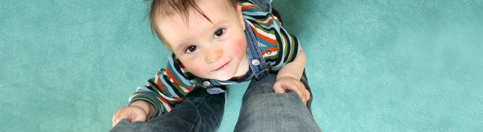 Ein Kind hält sich an den Hosbeinen seiner Mutter fest.