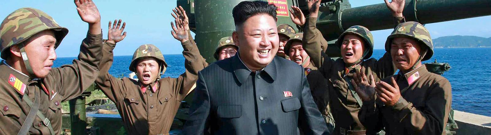 Nordkoreas Diktator Kim Jong-un wird am 07.07.2014 von ein paar Soldaten bejubelt und freut sich darüber.