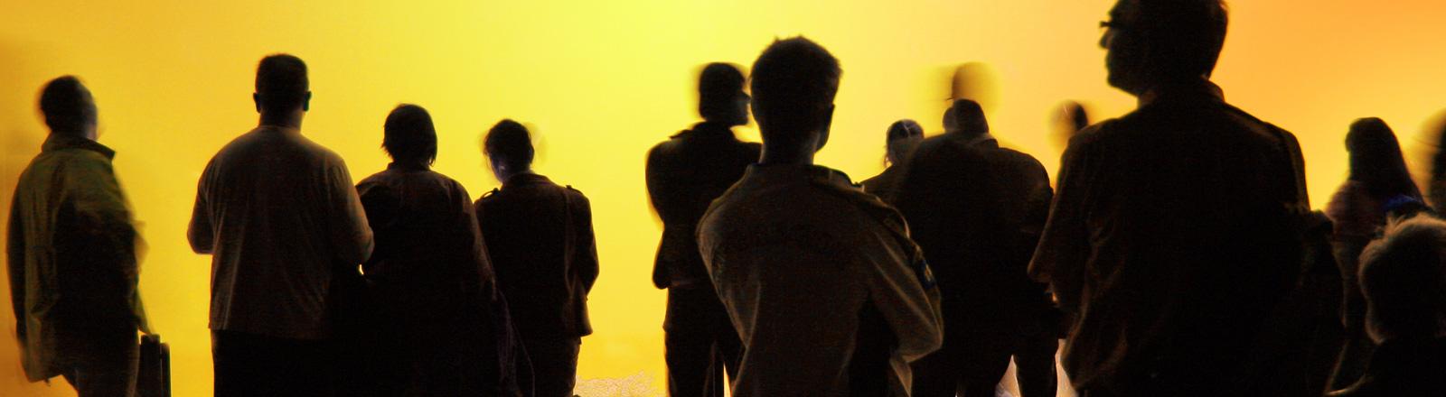 Vor einer gelben Wand stehen Männer und Frauen.