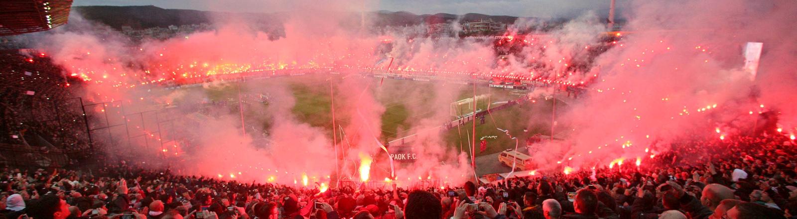 Feuerwerk bzw. bengalische Feuer brennen am 17.04.2014 während des Pokal-Halbfinales zwischen PAOK Saloniki und Olympiakos Piräus in der Toumba-Arena in Thessaloniki (Griechenland). Das Spiel begann mit 75 Minuten Verspätung und war von Schlägereien und schweren Ausschreitungen überschattet.