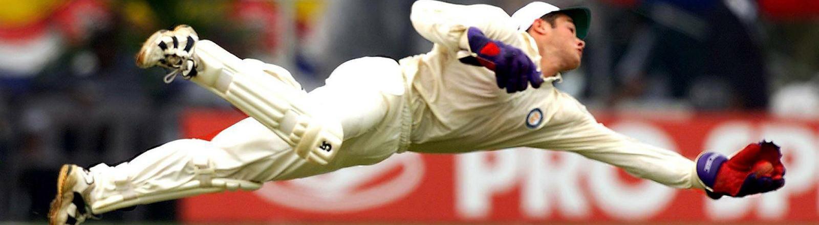 Der südafrikanische Kricketspieler Mark Boucher fliegt hoch durch die Luft, um eine Ball zu fangen.