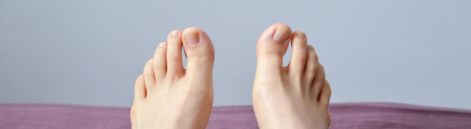 Zwei Füße schauen aus einer Bettdecke heraus.