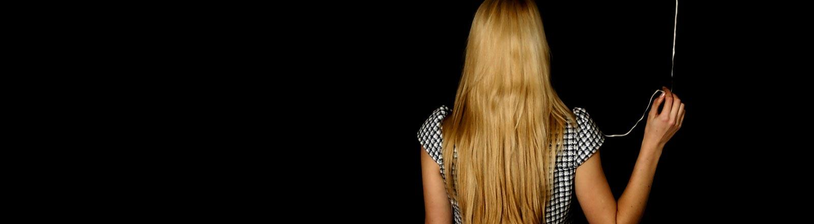 Eine Frau mit langen Haaren aus der Rückansicht.