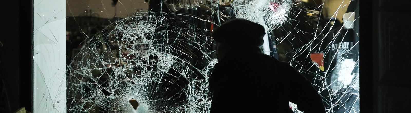 Ein Mensch läuft am 11.01.2016 im Stadtteil Connewitz in Leipzig (Sachsen) an einem beschädigtem Schaufenster vorbei. Rund 250 vermummte Hooligans haben am Montagabend in dem Leipziger Stadtteil randaliert. Sie hätten Pyrotechnik gezündet und Schaufensterscheiben mit Steinen eingeworfen, sagte eine Polizeisprecherin. Es handele sich um eine rechte Klientel aus dem Fußballbereich.