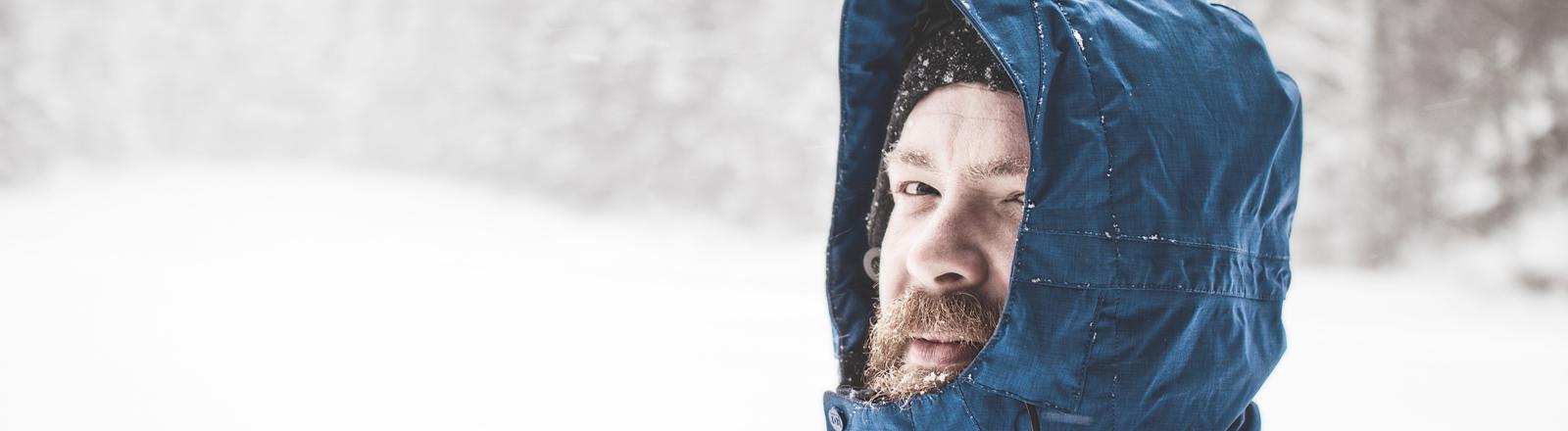 Mann im Winter mit Kapuze auf