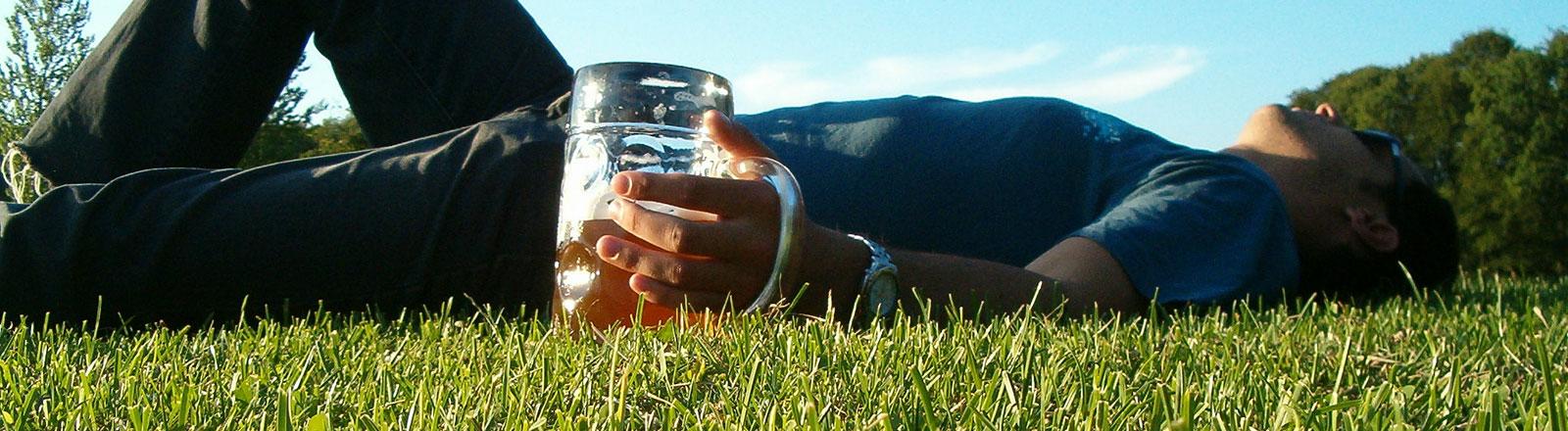 Mann mit Bierkrug auf Frühlingswiese