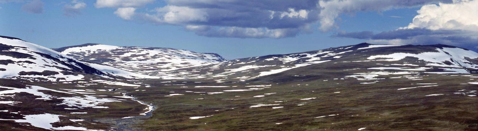 Blick über einen See auf die schneebeckten Hügel der Halti-Bergregion im finnischen Teil von Lappland, zu dem auch der Haltiatunturi gehört, der höchste Berg Finnlands.