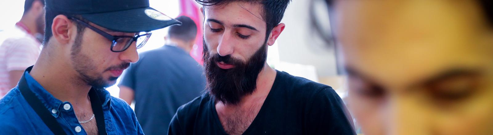 """Syrische Flüchtlinge schauen am 27.07.2016 in Berlin bei der Flüchtlingshilfe """"Moabit hilft"""" auf ein Smartphone. Hier ist ein aktuelles Video von einer verheerenden Bombadierung mit Toten und Verletzten aus Kamischli zu sehen."""