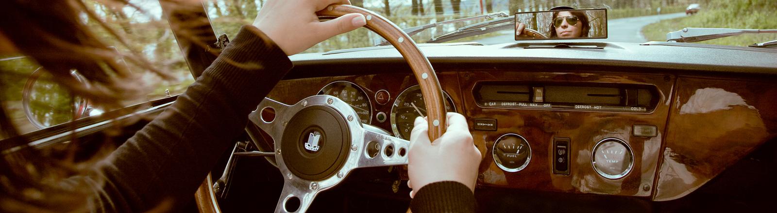 Frau sitzt in Cabrio am Lenkrad.