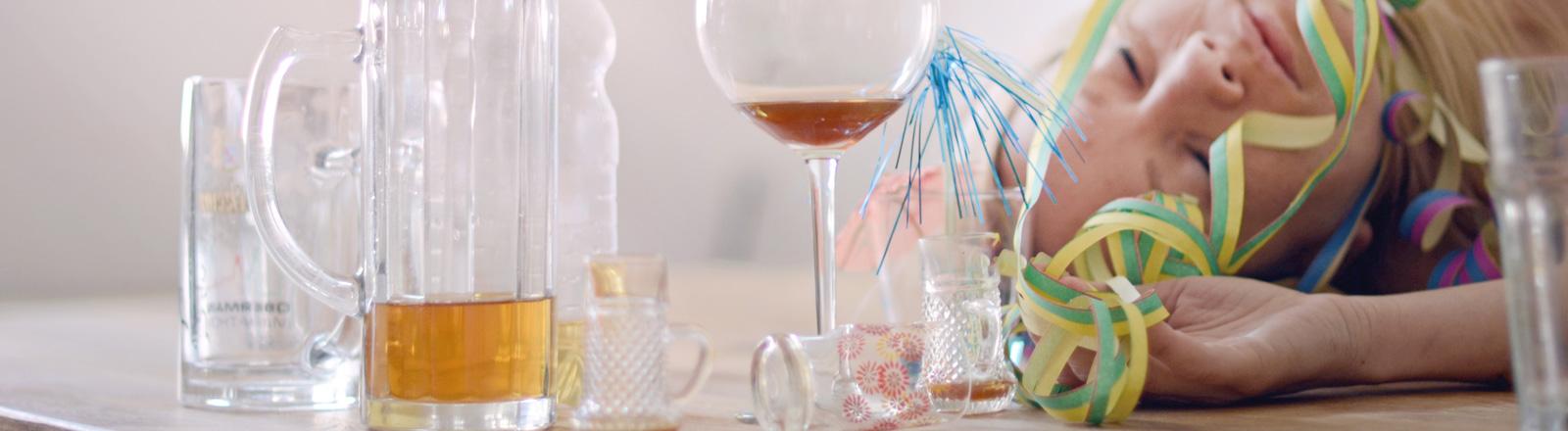 Eine betrunkene Frau liegt schlafende auf einem Tisch mit vielen leeren Gläsern.
