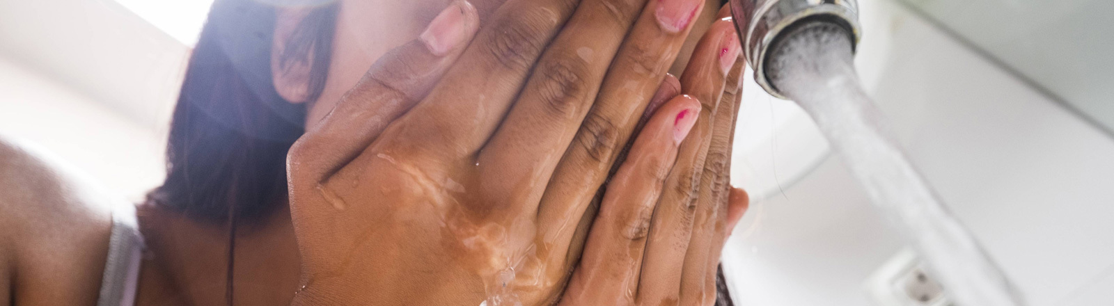 Eine Frau wäscht sich das Gesicht.