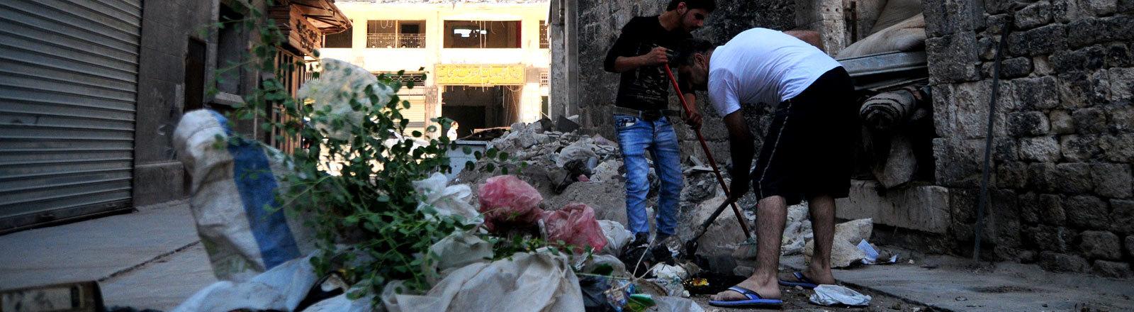 Zwei Syrer räumen am 24.06.2017 im Westen Aleppos Trümmer und Schutt von der Straße.