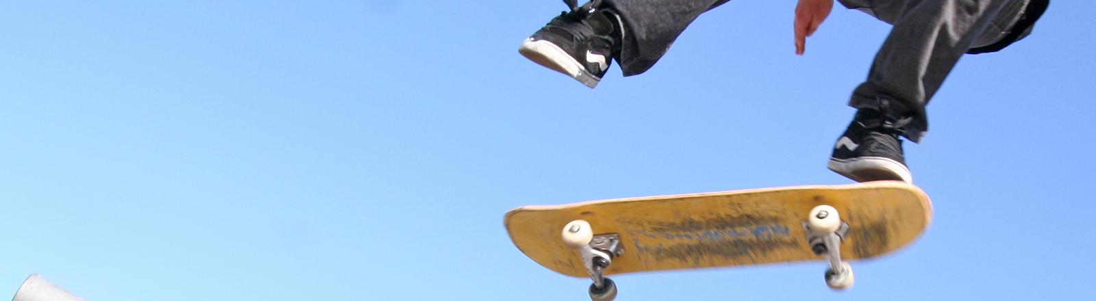 Ein Skateboard auf dem eine Person mit einem Bein steht, das andere schwebt darüber.