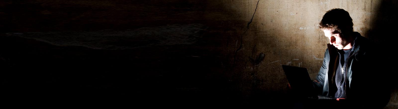 Ein Mann im dunklen Raum vor einem Notebook.