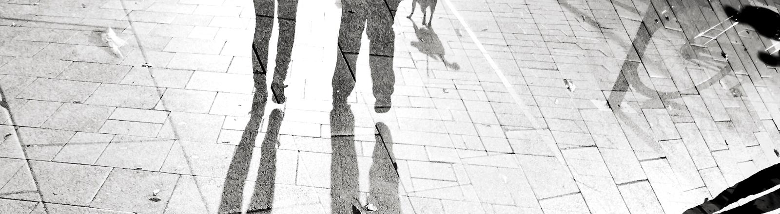 Die Schatten von zwei Menschen auf dem Asphalt, umringt von weiteren abstrakten Schatten.