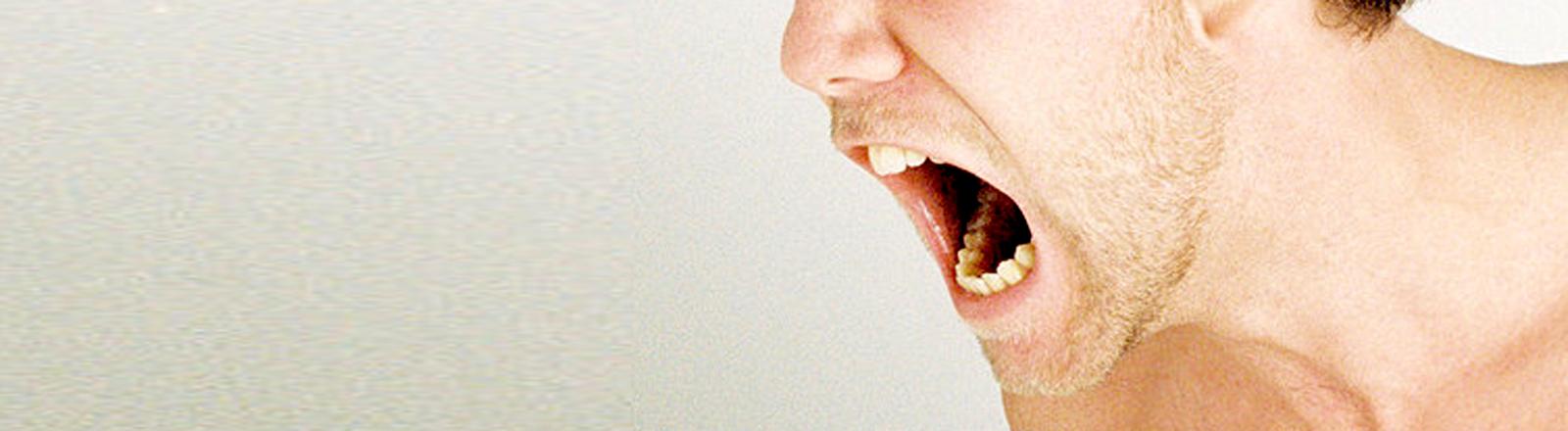 Ein junger Mann schreit mit aufgerissenem Mund.