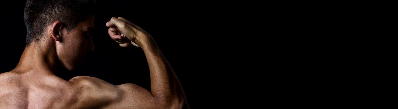Ein junger Mann spannt seine Muskeln an.