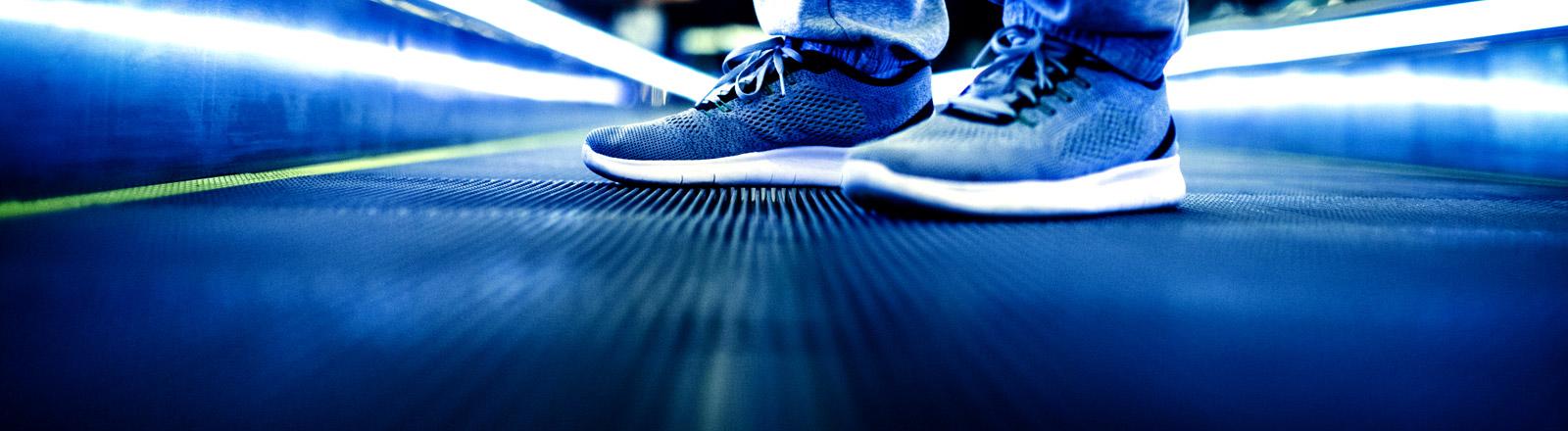 Ein Mann mit Sneakern auf einem Rollband