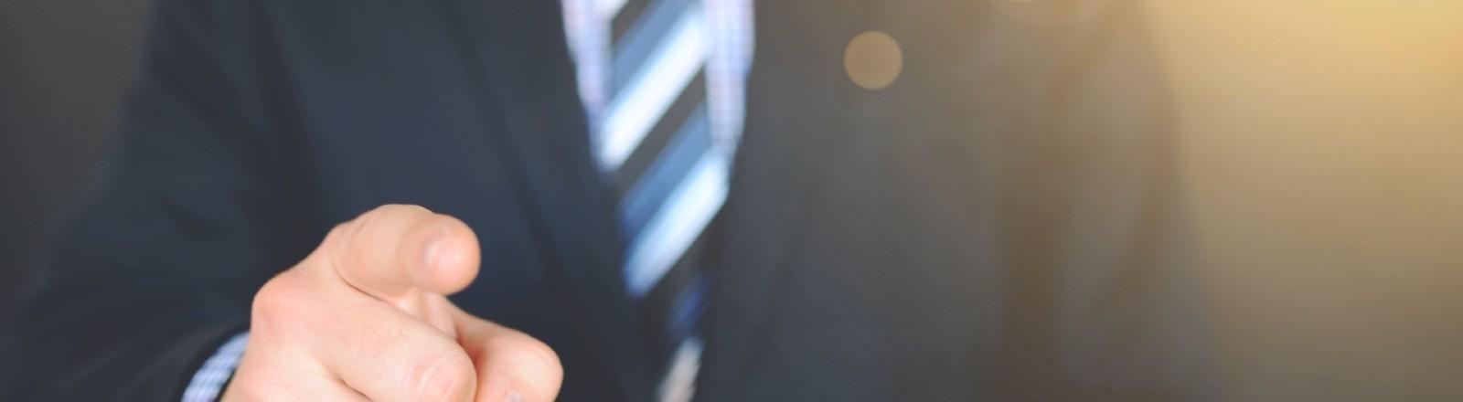 Ein Mann im Anzug zeigt mit dem Zeigefinger Richtung Kamera