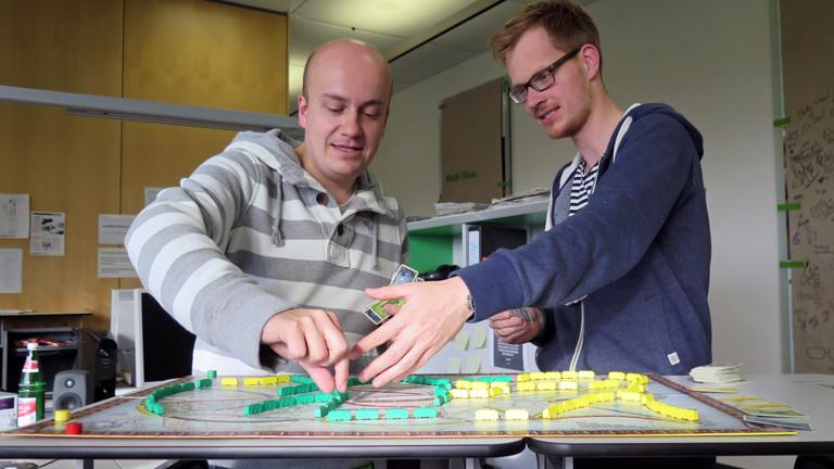 """Herr Pähler spielt mit den grünen Wagons, Daniel Fiene mit den gelben beim Brettspiel """"Ticket To Ride""""."""