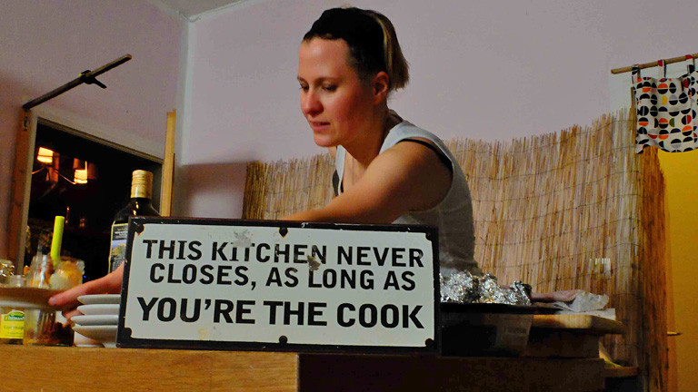 Eine Frau steht hinter einem Küchenbord. Auf diesem steht ein Schild mit dem Schriftzug: this kitchen never closes, as long as you're the cook.