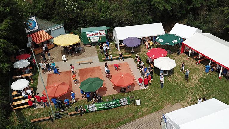 Blick auf den Platz für die deutsche Meisterschaft im Murmeln in Södel: Drei Murmelplätze nebeneinander, rund herum stehen Sonnenschirme und Zelte.